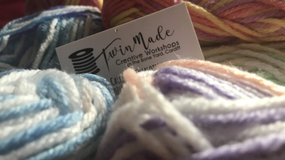 A business card reading Twin Made Studios sitting in a pile of multicoloured yarn