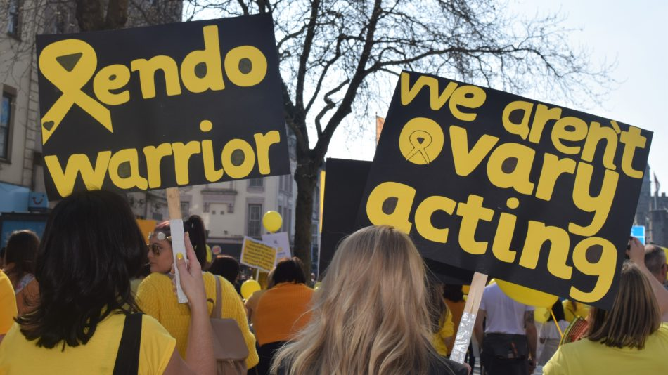"Two women carrying signs that read ""endo warrior"" and ""we aren't overary-acting"" to raise awareness for endometriosis"