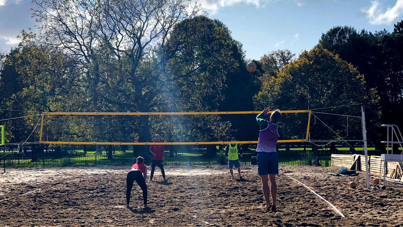 People are playing beach volleyball on the sand court