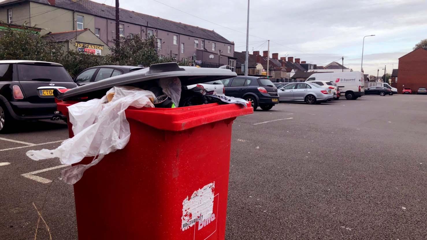 an overloaded bin in the car park