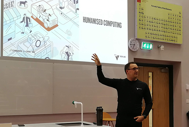 man giving presentation in lecture theatre gestures at projection screen