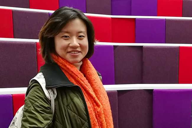 smiling student in lecture theatre with purple and red seats