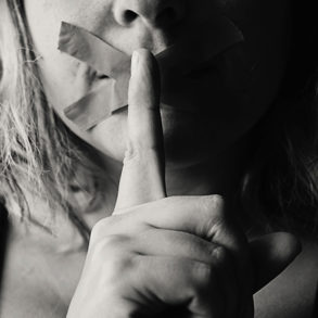 women with finger on her lip
