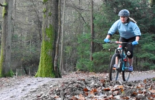 Laura riding down a trail at the Forest of Dean.
