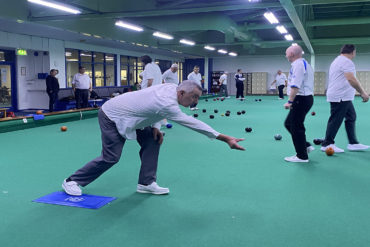 Man throwing a biased bowl towards the jack with other men playing bowls indoors behind him.