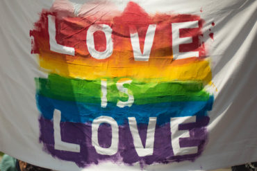 Rainbow banner that says 'Love is Love'